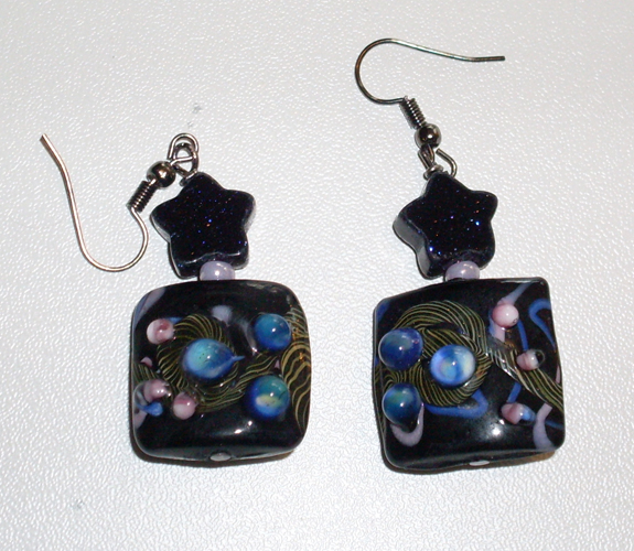 earrings: black square beads with planet inserts, plus stars