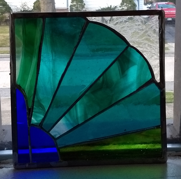 stained glass panel with navy peacock body and teal fan of tailfeathers